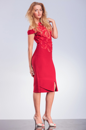 posing: side portrait of provocative blonde in red dress touching her shoulder in studio background, while looking at the camera