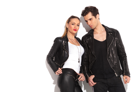 young fashion couple in leather clothes posing in studio, leaning on a white wall