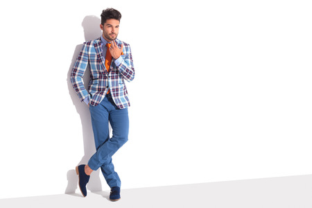 smart casual man standing in white studio background while touching his chin. his legs are crossed and has hand in pocket while looking away from the camera.