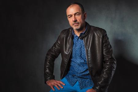 hombre sentado: Retrato de hombre maduro sentado en la chaqueta de cuero posando descansando sus manos mientras mira a la cámara en el estudio de fondo gris