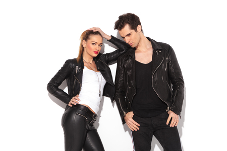 attractive girl: relaxed fashion couple in leather clothes posing in studio, woman leaning on her lovers shoulder