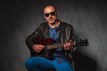 hombres maduros: retrato de rocker madura sentado en la chaqueta de cuero que toca la guitarra eléctrica mientras mira a la cámara en el fondo gris del estudio Foto de archivo