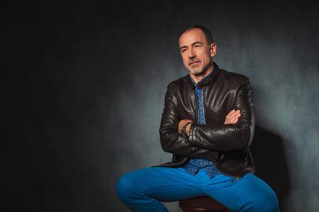 mani incrociate: Ritratto di uomo maturo seduto in giacca di pelle in posa in cerca di distanza con le mani incrociate in sfondo grigio studio Archivio Fotografico