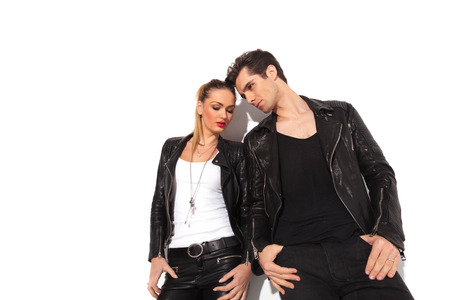 next to each other: young couple in leather clothes standing next to each other with hands in pockets