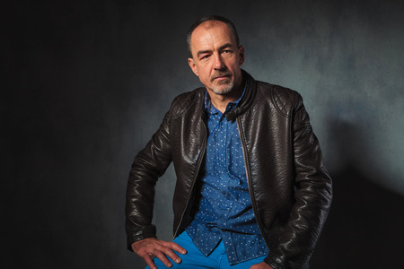mature man: portrait of seated mature man in leather jacket resting his hands while looking away from the camera in gray studio background