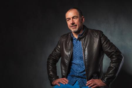 hombres maduros: Retrato de hombre maduro sentado en manos de descanso chaqueta de cuero mientras se mira lejos de la cámara en el estudio de fondo gris Foto de archivo