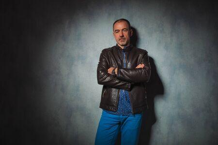 mani incrociate: elegante uomo anziano in giacca di pelle in posa in sfondo grigio studio con le mani incrociate, mentre guardando la telecamera