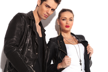 head collar: closeup picture of a young fashion couple in leather jackets, woman holding her collar and man standing next to her in studio Stock Photo