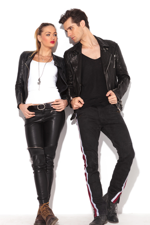 fashion clothes: young fashion couple in leather clothes looking at each other, full body picture, leaning on a white wall Stock Photo