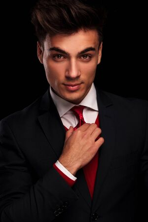dark red: close portrait of handsome male model in black suit fixing his red tie while looking at the camera in dark studio background