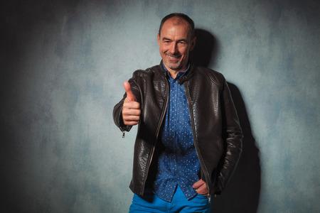hombres maduros: retrato de hombre maduro en la chaqueta de cuero que muestran los pulgares para arriba con la mano en el bolsillo mientras mira a la cámara en el fondo gris del estudio