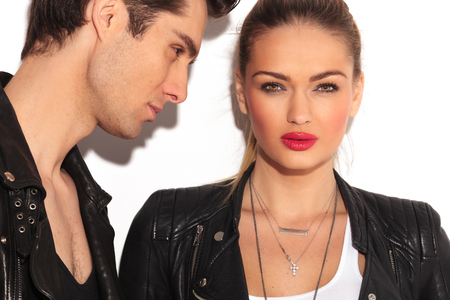 beautiful black woman: blonde woman in leather jacket looks to  the camera while her boyfriend is looking at her; closeup picture of a young couple in leather jackets