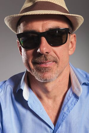 open shirt: closeup portrait of bearded man with open shirt, wearing brown hat and black sunglasses looking at the camera in gray studio background Stock Photo