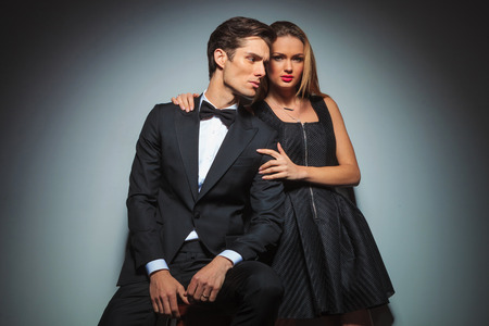 attractive couple in black posing in studio background, she looking at the camera while embracing him. man looks away from the camera. Stockfoto