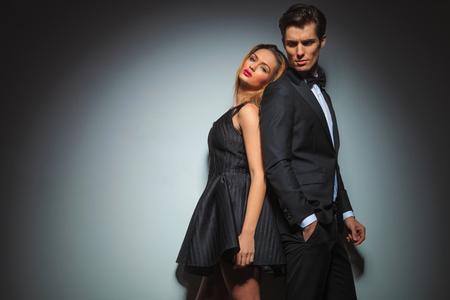 espalda con espalda elegante pareja posando en el estudio de fondo gris. Foto de archivo