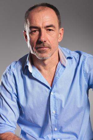 open shirt: closeup of mature smart casual man with blue open shirt posing in gray studio background while looking at the camera