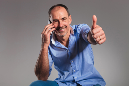 old man happy: portrait of seated casual senior man talking on his mobile while showing thumbs up sign.