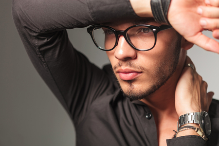 close up view: side view of a young man with glasses with hand on forehead looks away from the camera
