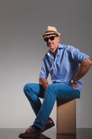 hombre sentado: Retrato de hombre maduro ocasional sentado mientras llevaba sombrero y gafas de sol negras con la mano en la cintura.