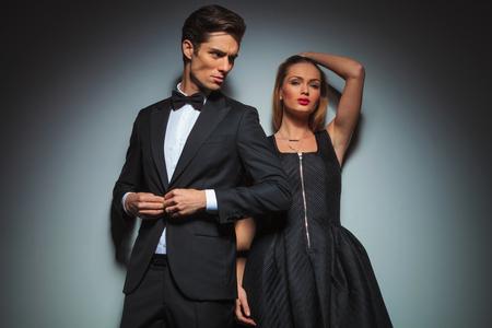 pareja elegante en la presentación en negro sobre fondo gris de estudio.