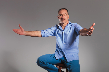 male models: portrait of seated casual man welcoming with open arms while looking at the camera in gray studio background