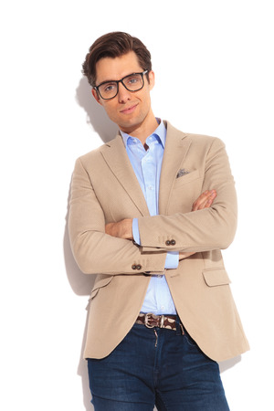 mani incrociate: ritratto di uomo attraente smart casual in jeans posa in studio isolato sfondo con le mani incrociate, guardando la telecamera Archivio Fotografico