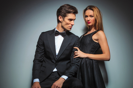 beautiful hands: sensual couple in black posing in studio background. man in suit is seated looking at woman while she is embracing his arm looking at the camera. Stock Photo