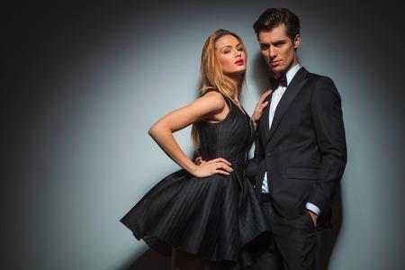 pareja elegante en negro posando juntos en el estudio de fondo gris.