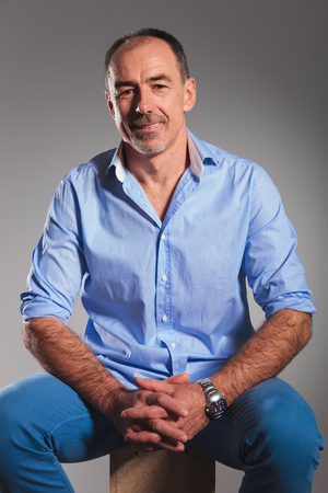 casual clothing: closeup portrait of mature man in open blue shirt with hands together posing seated in gray studio background while looking at the camera Stock Photo