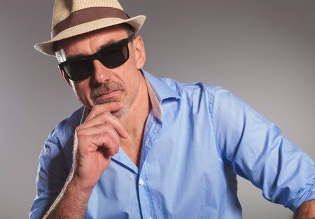 open shirt: closeup portrait of pensive mature man with open shirt wearing black sunglasses and brown hat, looking at the camera in gray studio background Stock Photo