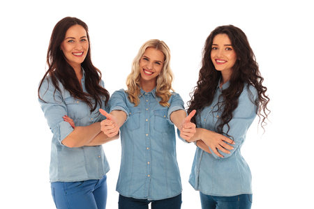 woman hands up: young blonde woman making the ok thumbs up sign while her friends are standing with hands crossed on white background