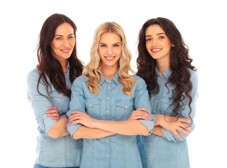 mani incrociate: tre donne casuali fiducioso in piedi con le mani incrociate su sfondo bianco studio