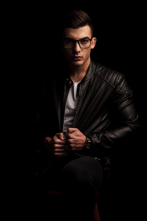 dark haired: portrait of seated dark haired macho man in black leather jacket and white shirt wearing glasses while pulling his jacket and looking at the camera in isolated black studio background Stock Photo