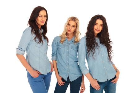 tre modelli di modo in azzurri jeans vestiti in piedi su sfondo bianco