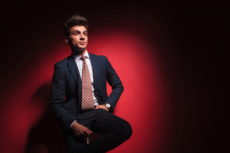 legs crossed: young businessman in black suit with red tie posing seated with hand in pocket and legs crossed while looking away from the camera in red studio background Stock Photo