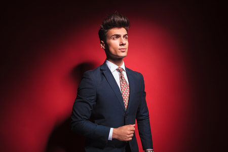classy: portrait of confident young businessman in black suit with red tie posing arranging his jacket and looking away from the camera in red studio background