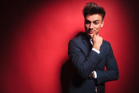 uomo rosso: Ritratto di uomo d'affari astuto casuale nel pensiero nero con le mani incrociate mentre guardando lontano dalla telecamera in studio sfondo rosso