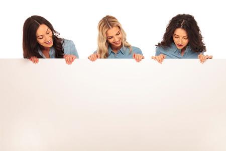 Drie gelukkige jonge casual vrouw naar beneden te kijken naar een grote lege bord op een witte achtergrond Stockfoto