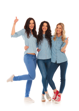 squadra di giovani donne casuali che fanno il pollice in alto segno ok su sfondo bianco