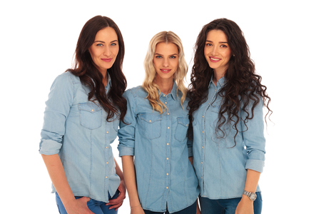 three women: three women friends standing together and looking at the caemra on white background