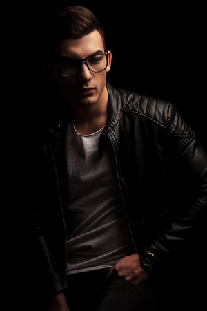 dark haired: portrait of attractive dark haired young man in black leather jacket and white shirt wearing frames while resting with hand on waist looking away from the camera in isolated black studio background