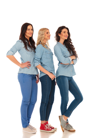 up view: full body picture of 3 casual women standing in line and looking up to something  on white studio background