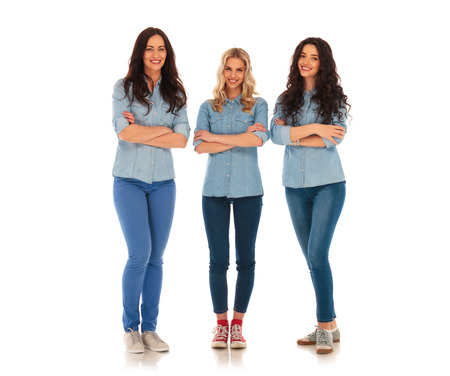 full body picture of three confident casual women standing on white studio background with hands crossed