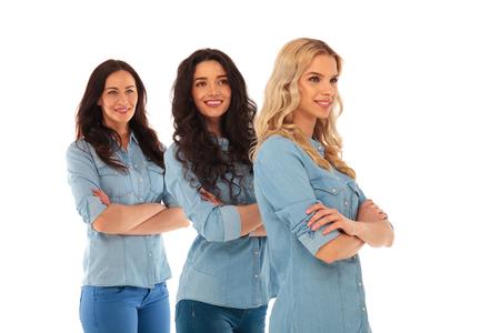 mani incrociate: vista laterale di tre donne casuali fiduciosi in piedi con le mani incrociate su sfondo bianco e guardando lontano dalla fotocamera