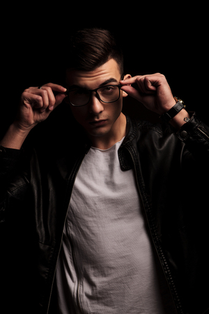 dark haired: portrait of fashionable dark haired man in black leather jacket and white shirt taking off his glasses while looking at the camera in isolated black studio background Stock Photo