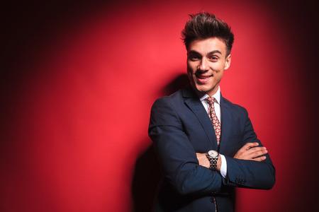 mani incrociate: Ritratto di giovane uomo d'affari in abito nero con cravatta rossa, che propone le mani incrociate in studio sfondo rosso, mentre guardando la telecamera e sogghignando