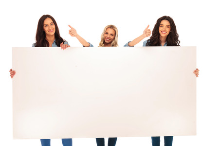 3 happy casual women recommend what they are showing you on a big blank board, making the ok thumbs up hand sign on white background