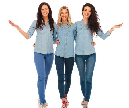 3 mujeres ocasionales felices que recorren y darle la bienvenida a su equipo, en el fondo blanco del estudio