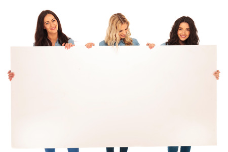 empty of people: three women friends holding a blank billboard and smile on white background Stock Photo