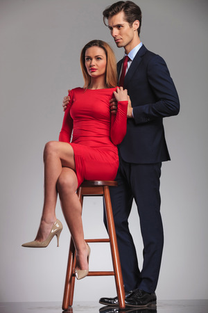 side view of young businessman holding seated woman in red dress by shoulders and both look away from the camera